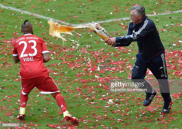 TOPSHOT Bayern Munich's Italian head coach Carlo Ancelotti pours beer over Chilean midfielder Arturo Vidal after the German first division Bundesliga...
