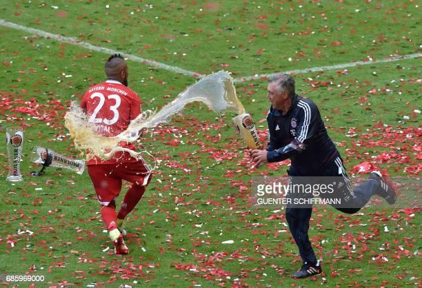 Bayern Munich's Italian head coach Carlo Ancelotti pours beer over Chilean midfielder Arturo Vidal after the German first division Bundesliga...