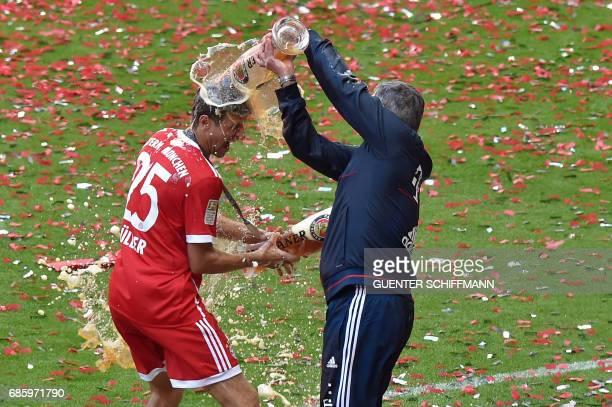 Bayern Munich's Italian head coach Carlo Ancelotti pours beer over Bayern Munich's forward Thomas Mueller after the German first division Bundesliga...