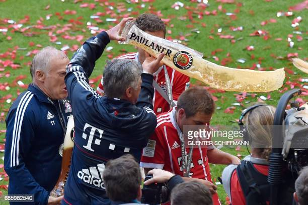 Bayern Munich's Italian head coach Carlo Ancelotti pours beer over Bayern Munich's defender Philipp Lahm after the German first division Bundesliga...