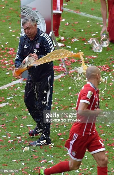 Bayern Munich's Italian head coach Carlo Ancelotti throws beer towards Bayern Munich's Dutch midfielder Arjen Robben after the German first division...