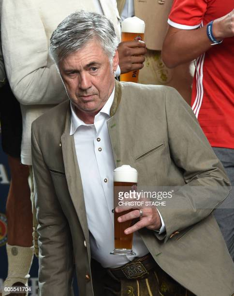 Bayern MunichÕs Italian headcoach Carlo Ancelotti holds a beer as he poses along with his team's members in typicial Bavarian clothes during a...
