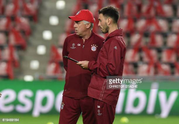 Bayern Munich's Italian headcoach Carlo Ancelotti speaks with his assistant coach and son Davide Ancelotti during a training session at the stadium...