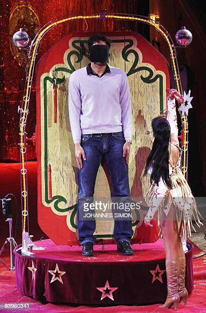 Bayern Munich's Italian striker Luca Toni is blindfolded as a knife thrower performs with him during the FC Bayern Circus Gala at the Circus Krone on...