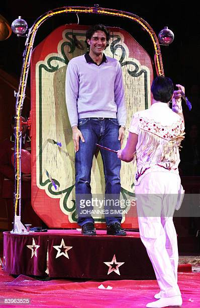 Bayern Munich's Italian striker Luca Toni watches a knife thrower pointing his knife at him during the FC Bayern Circus Gala at the Circus Krone on...
