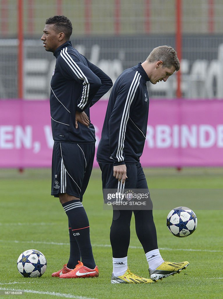 Bayern Munich's midfielder Bastian Schweinsteiger (R) kicks the ball beside of his teammate Bayern Munich's defender Jerome Boateng during the final team training on the eve of the UEFA Champions League semi final first leg football match between FC Bayern Munich and FC Barcelona at the trainings area in Munich, southern Germany, on April 22, 2013. The semi final match will take place on April 23, 2013.