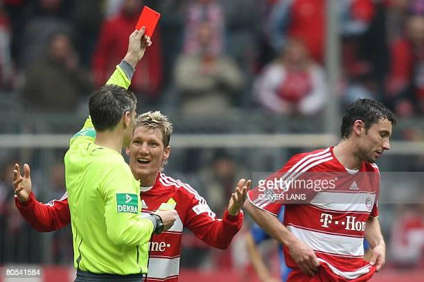 DFL Bayern Munich's midfielder Bastian Schweinsteiger protests as referee Michael Weiner shows the red card to Dutch midfielder Mark van Bommel...