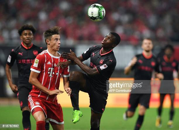 Bayern Munich's midfielder Corentin Tolisso and Arsenal Eddie Nketiah vie for the ball during the International Champions Cup football match between...