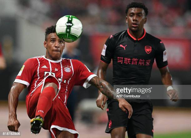 Bayern Munich's midfielder Corentin Tolisso and Arsenal forward Alex Iwobi vie for the ball during the International Champions Cup football match...