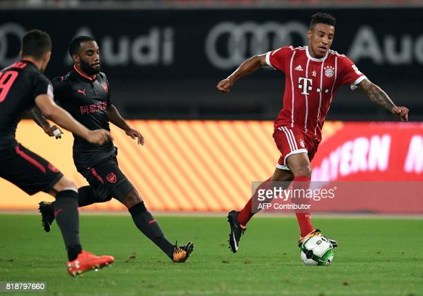 Bayern Munich's midfielder Corentin Tolisso and Arsenal forward Alexandre Lacazette vie for the ball during the International Champions Cup football...