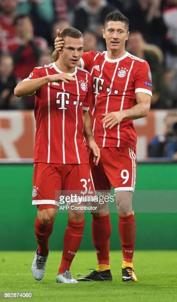 Bayern Munich's midfielder Joshua Kimmich celebrates scoring with Bayern Munich's Polish striker Robert Lewandowski during the Champions League group...