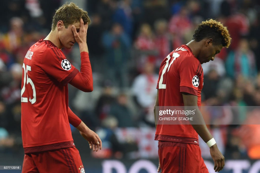 Bayern Munich's midfielder Thomas Mueller (L) and Bayern Munich's French defender Kingsley Coman leave the pitch after the UEFA Champions League semi-final, second-leg football match between FC Bayern Munich and Atletico Madrid in Munich, southern Germany, on May 3, 2016. / AFP / Christof Stache
