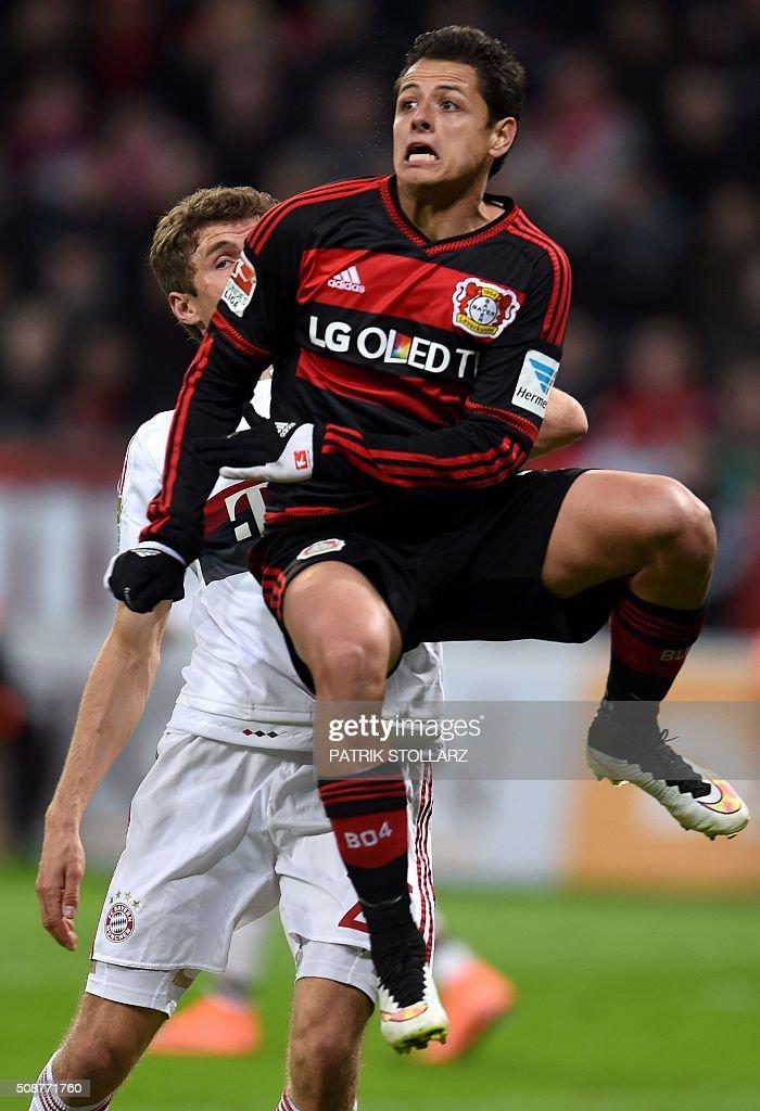 Bayern Munich's midfielder Thomas Mueller and Leverkusen's Mexican striker Javier Hernandez vie for the ball during the German first division Bundesliga football match of Bayer 04 Leverkusen v Bayern Munich in Leverkusen, western Germany, on February 6, 2016. / AFP / PATRIK STOLLARZ /
