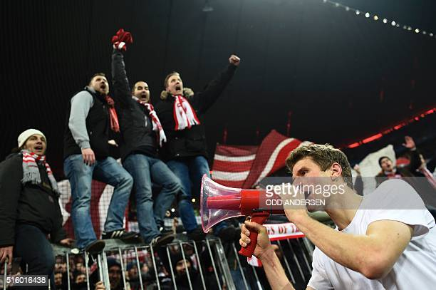 Bayern Munich's midfielder Thomas Mueller celebrates win fans after the UEFA Champions League Round of 16 second leg football match FC Bayern Munich...