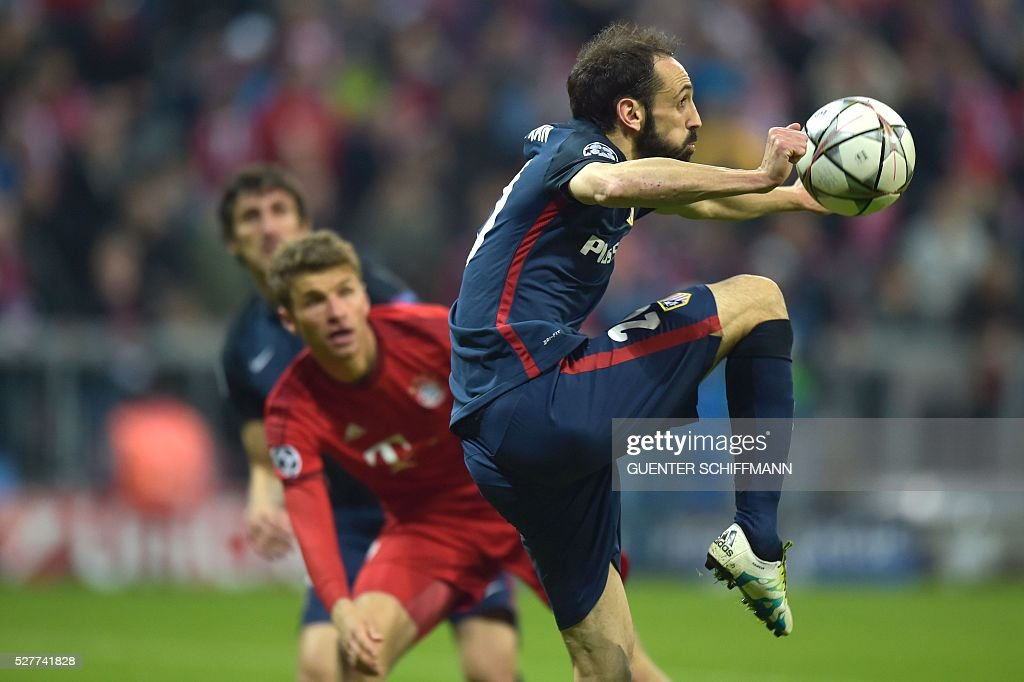 Bayern Munich's midfielder Thomas Mueller (2ndL) looks as Atletico Madrid's defender Juanfran (R) plays the ball during the UEFA Champions League semi-final, second-leg football match between FC Bayern Munich and Atletico Madrid in Munich, southern Germany, on May 3, 2016. / AFP / GUENTER