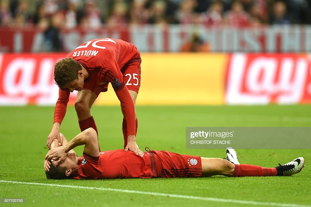 Bayern Munich's midfielder Thomas Mueller (up) speaks to Bayern Munich's Polish striker Robert Lewandowski lying on the pitch during the UEFA Champions League semi-final, second-leg football match between FC Bayern Munich and Atletico Madrid in Munich, southern Germany, on May 3, 2016. / AFP / Christof Stache