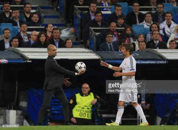 Bayern Munich's Pep Guardiola hands the ball to Real Madrid's Fabio Coentrao