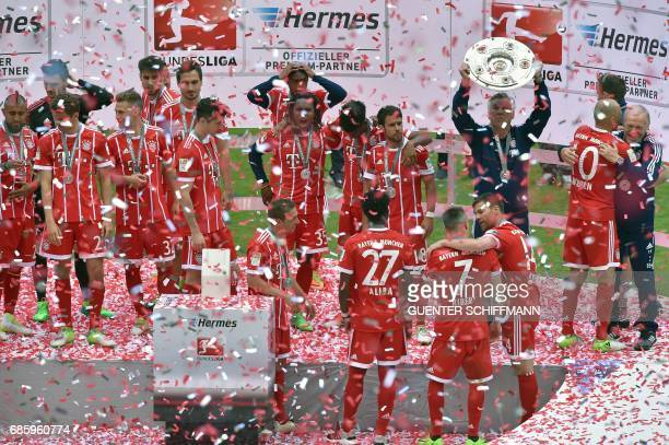 Bayern Munich's players and Bayern Munich's Italian head coach Carlo Ancelotti celebrate with the trophy after the German first division Bundesliga...