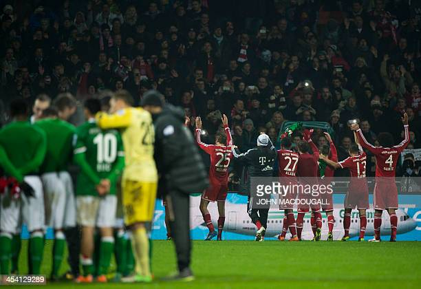 Bayern Munich's players celebrate with fans as Bremen players form a circle after the German first division Bundesliga football match between SV...