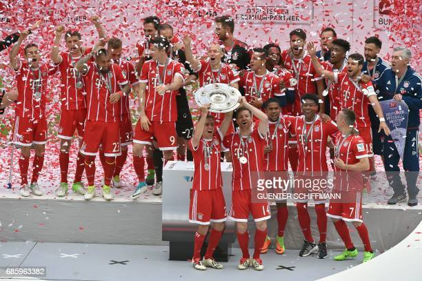 Bayern Munich's players including defender Philipp Lahm and Spanish midfielder Xabi Alonso celebrate with the trophy after the German first division...