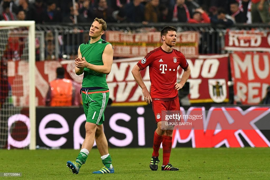 Bayern Munich's players including Spanish midfielder Xabi Alonso (R) and Bayern Munich's goalkeeper Manuel Neuer react after the UEFA Champions League semi-final, second-leg football match between FC Bayern Munich and Atletico Madrid in Munich, southern Germany, on May 3, 2016. / AFP / LUKAS