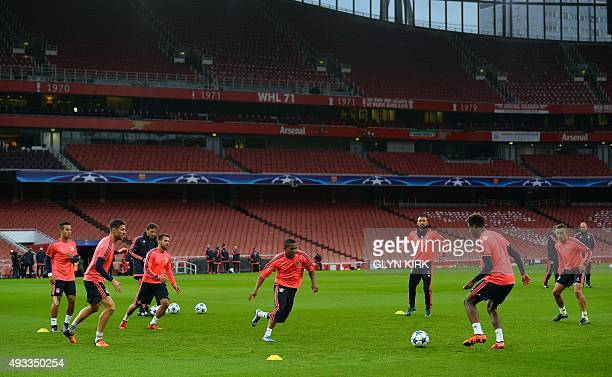 Bayern Munich's players pass the ball during a team training session at the Emirates Stadium in London on October 19 on the eve of their UEFA...