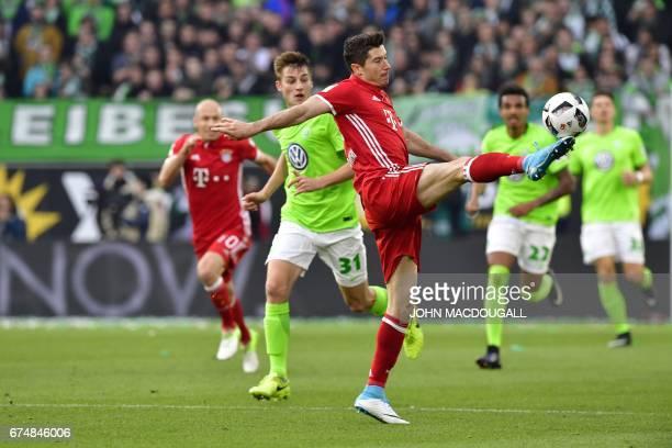 Bayern Munich's Polish forward Robert Lewandowski and Wolfsburg's defender Robin Knoche vie for the ball during the German first division Bundesliga...