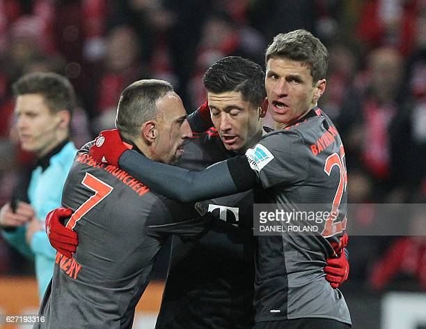 Bayern Munich's Polish forward Robert Lewandowski celebrates scoring with his teammates French midfielder Franck Ribery and forward Thomas Mueller...