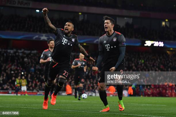 Bayern Munich's Polish forward Robert Lewandowski celebrates with Bayern Munich's Chilean midfielder Arturo Vidal after scoring a penalty during the...