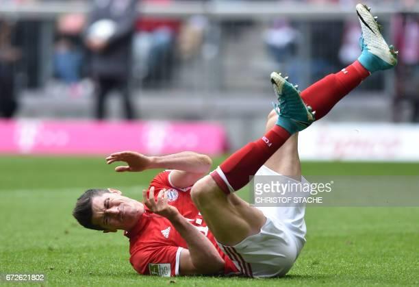 Bayern Munich's Polish forward Robert Lewandowski falls on the pitch during the German first division Bundesliga football match between FC Bayern...