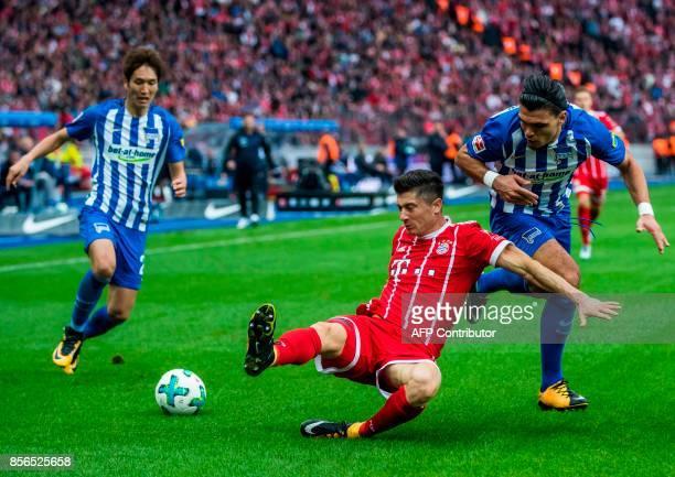 Bayern Munich's Polish forward Robert Lewandowski Hertha Berlin´s Dutch defender Karim Rekik and Hertha Berlin's Japanese midfielder Genki Haraguchi...