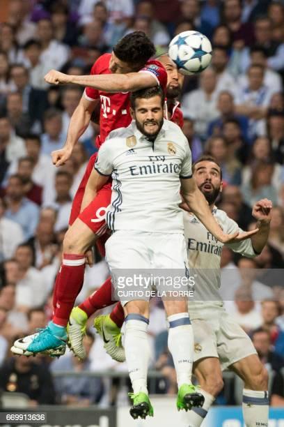 Bayern Munich's Polish forward Robert Lewandowski jumps for the ball with Real Madrid's defender Dani Carvajal during the UEFA Champions League...