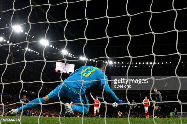Bayern Munich's Polish forward Robert Lewandowski scores a penalty past Arsenal's Colombian goalkeeper David Ospina during the UEFA Champions League...