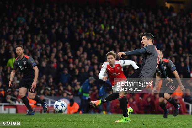 Bayern Munich's Polish forward Robert Lewandowski scores from a penalty during the UEFA Champions League last 16 second leg football match between...