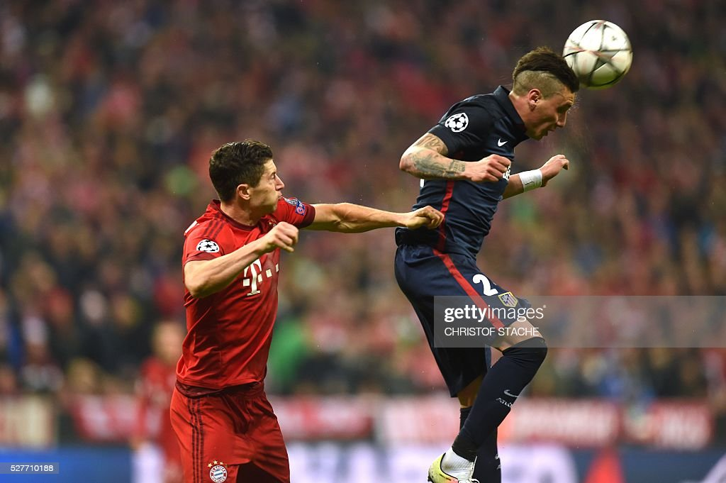 Bayern Munich's Polish striker Robert Lewandowski (L) and Atletico Madrid's Uruguayan defender Jose Maria Gimenez fight for the ball during the UEFA Champions League semi-final, second-leg football match between FC Bayern Munich and Atletico Madrid in Munich, southern Germany, on May 3, 2016. / AFP / Christof Stache