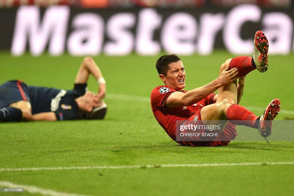 Bayern Munich's Polish striker Robert Lewandowski (R) and Atletico Madrid's Brazilian defender Filipe Luis react after clashing during the UEFA Champions League semi-final, second-leg football match between FC Bayern Munich and Atletico Madrid in Munich, southern Germany, on May 3, 2016. / AFP / Christof Stache