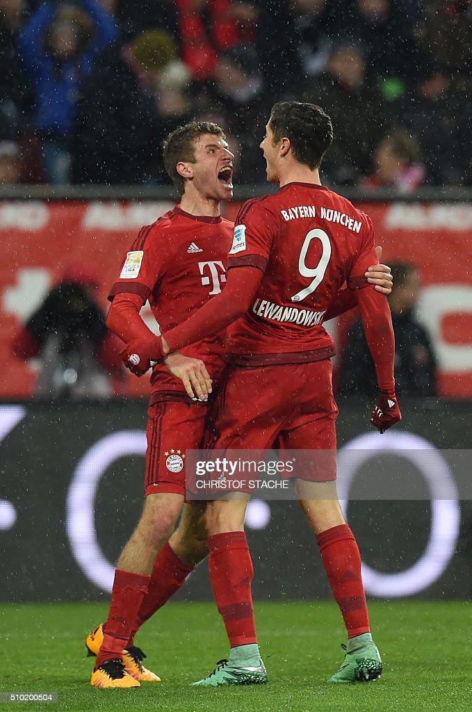 Bayern Munich's Polish striker Robert Lewandowski (R) and Bayern Munich's striker Thomas Mueller celebrate after Lewandowski scored the 0-1 goal during the German first division Bundesliga football match of FC Augsburg vs FC Bayern Munich in Augsburg, southern Germany, on February 14, 2016. / AFP / CHRISTOF STACHE /