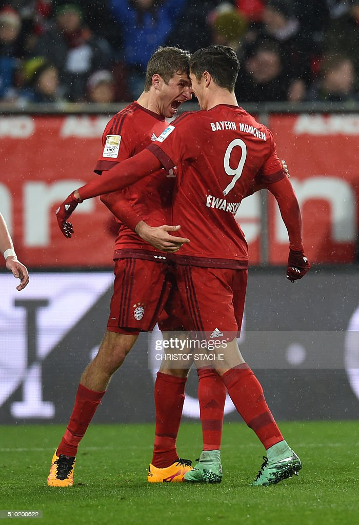 Bayern Munich's Polish striker Robert Lewandowski (R) and Bayern Munich's striker Thomas Mueller celebrate after Lewandowski scored the 0-1 goal during the German first division Bundesliga football match of FC Augsburg vs FC Bayern Munich in Augsburg, southern Germany, on February 14, 2016. / AFP / CHRISTOF STACHE /