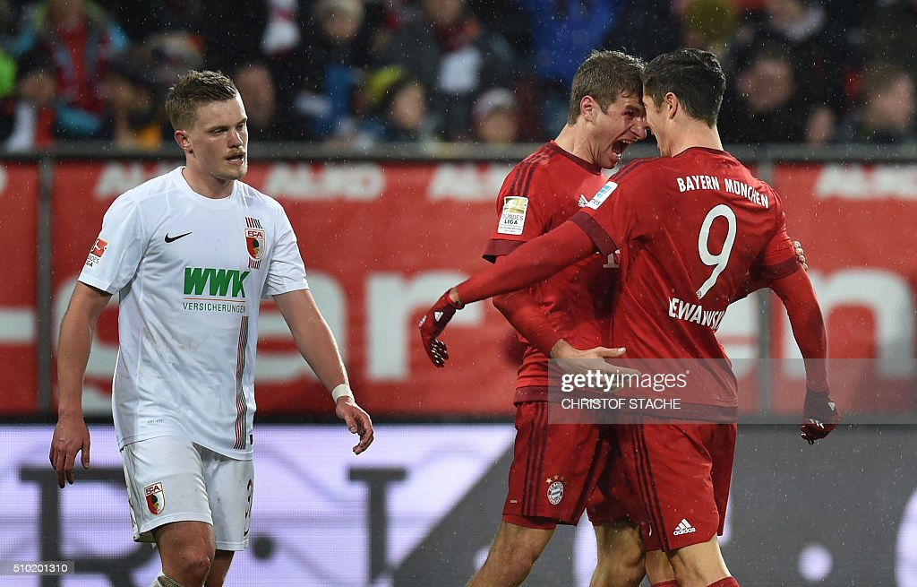 Bayern Munich's Polish striker Robert Lewandowski (R) and Bayern Munich's striker Thomas Mueller celebrate after Lewandowski scored the 0-1 goal next to Augsburg's defender Max Philipp (L) during the German first division Bundesliga football match of FC Augsburg vs FC Bayern Munich in Augsburg, southern Germany, on February 14, 2016. / AFP / CHRISTOF STACHE /