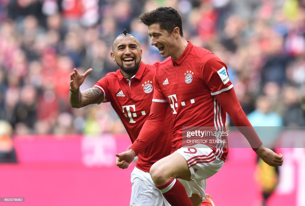 Bayern Munich's Polish striker Robert Lewandowski (R) and Bayern Munich's Chilean midfielder Arturo Vidal (L) celebrate after the third goal for Munich during the German First division Bundesliga football match Bayern Munich vs Eintracht Frankfurt in Munich, southern Germany, on March 11, 2017. / AFP PHOTO / Christof
