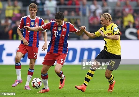 Bayern Munich's Polish striker Robert Lewandowski and Dortmund's defender Marcel Schmelzer vie for the ball vie during the German Supercup football...