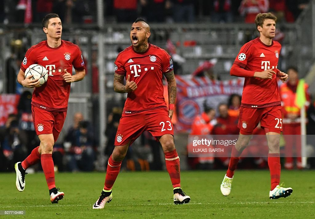 Bayern Munich's Polish striker Robert Lewandowski celebrates scoring with his team-mates Chilean midfielder Arturo Vidal (C) and Bayern Munich's midfielder Thomas Mueller during the UEFA Champions League semi-final, second-leg football match between FC Bayern Munich and Atletico Madrid in Munich, southern Germany, on May 3, 2016. / AFP / LUKAS