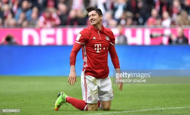 Bayern Munich's Polish striker Robert Lewandowski knees on the pitch during the German First division Bundesliga football match Bayern Munich vs...