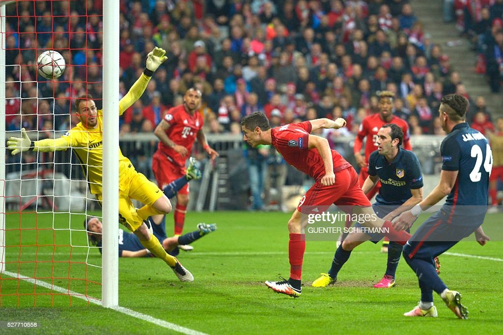 Bayern Munich's Polish striker Robert Lewandowski (C) scores past Atletico Madrid's Slovenian goalkeeper Jan Oblak (L) during the UEFA Champions League semi-final, second-leg football match between FC Bayern Munich and Atletico Madrid in Munich, southern Germany, on May 3, 2016. / AFP / GUENTER