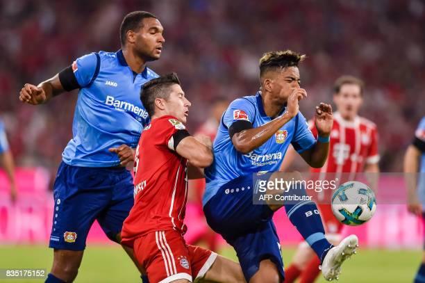 Bayern Munich's Polnish striker Robert Lewandowski and Leverkusen's German defender Benjamin Henrichs vie for the ball during the German First...
