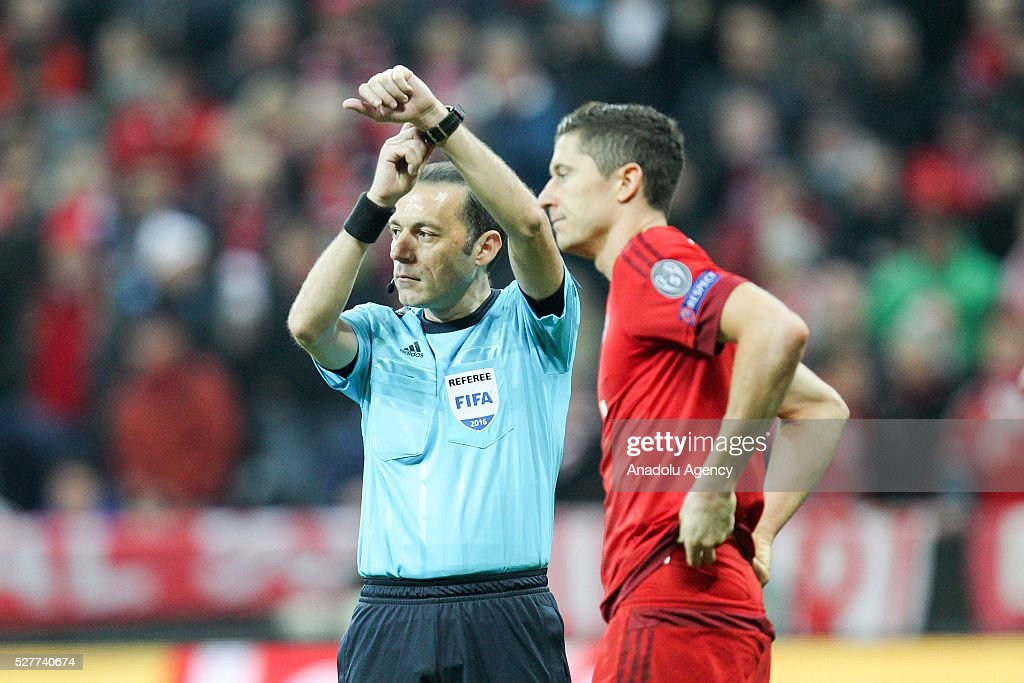 Bayern Munich's Robert Lewandowski (R) stands next to the referee Cuneyt Cakir conducts the UEFA Champions League semifinal second leg soccer match between FC Bayern Munich and Atletico Madrid at the Allianz Arena in Munich, Germany on May 3, 2016.