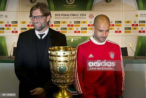 Bayern Munich's Spanish head coach Pep Guardiola and Dortmund's head coach Juergen Klopp pose with the trophy after a press conference at Berlin's...