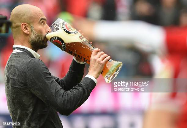 Bayern Munich's Spanish head coach Pep Guardiola drinks a beer as he celebrates with the team winning the Bundesliga after the German first division...