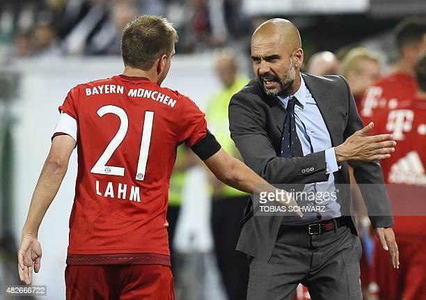 Bayern Munich's Spanish head coach Pep Guardiola talks to Bayern Munich's defender Philipp Lahm during the German Supercup football match VfL...