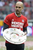 Bayern Munich's Spanish headcoach Pep Guardiola holds the trophy as they celebrate winning their 25th Bundesliga title after the German first...